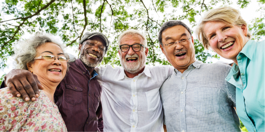 Group of older people hugging and smiling at camera