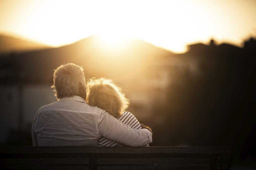 elderly couple looking at sunset over mountain