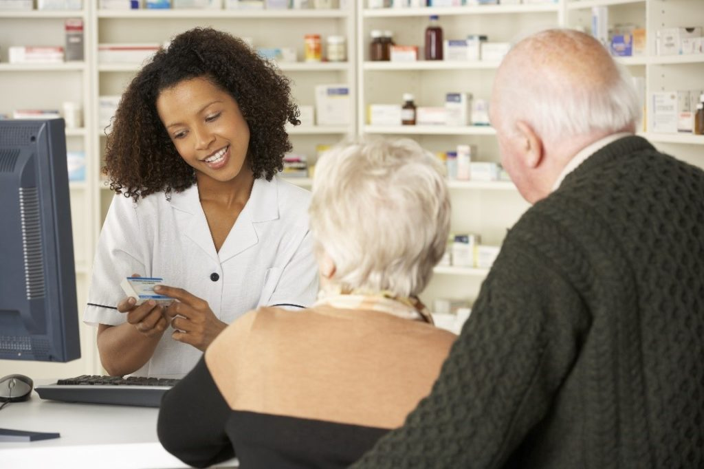 pharmacist communicating with elderly couple